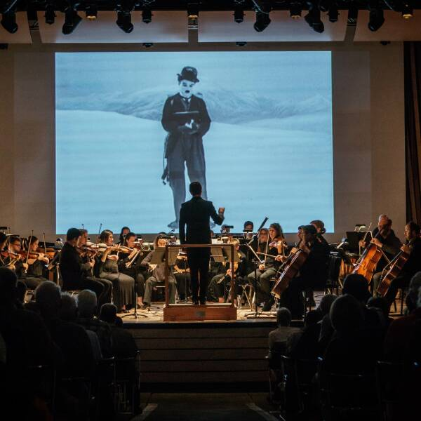 The orchestra performs while Charlie Chaplin videos play in the back
